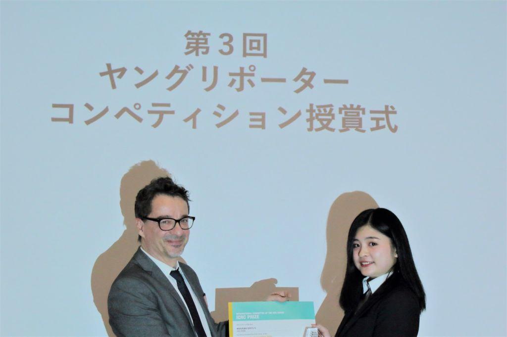 ICRC駐日代表レジス・サビオよりICRC賞の賞状とトロフィーを受け取る石田さん(右)