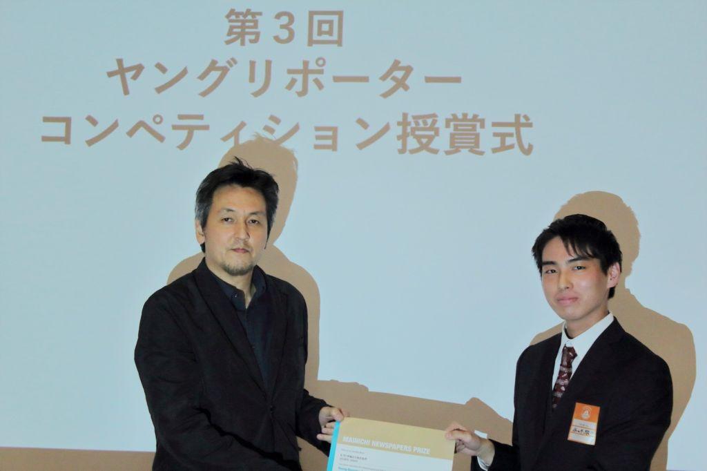 毎日新聞社の佐藤賢二郎氏より表彰される佐々木さん(右)