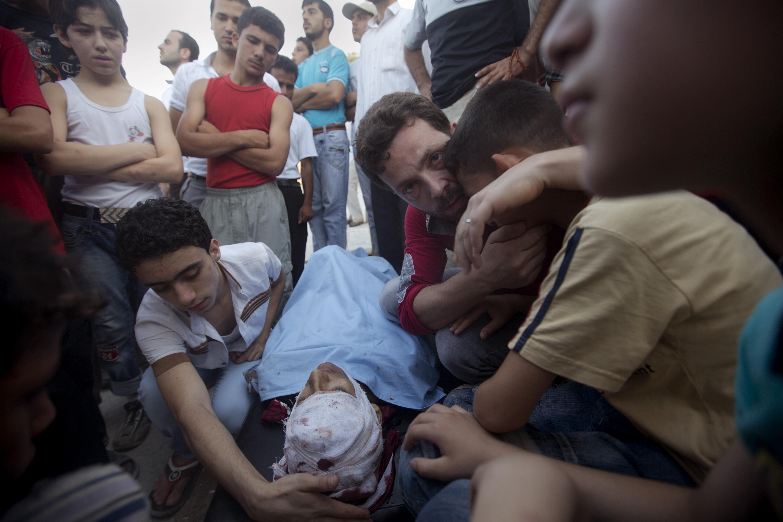亡くなった息子を前に嘆き悲しむもう一人の息子を抱きしめ、こちらを見つめる父親